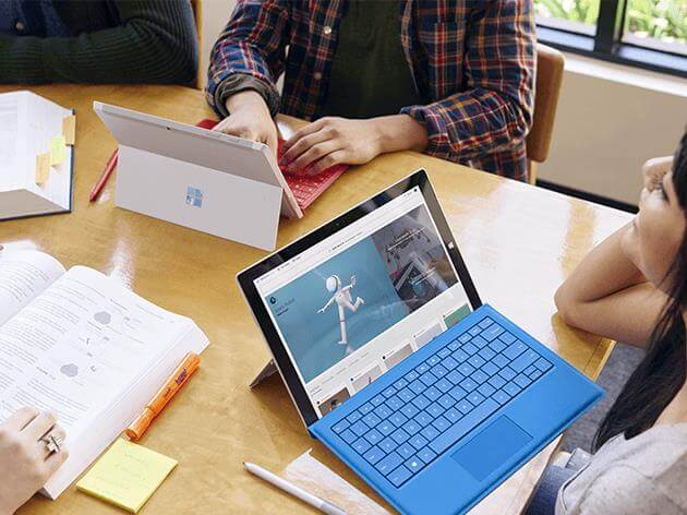 Young people collaborate to create 3D image in Paint 3D.