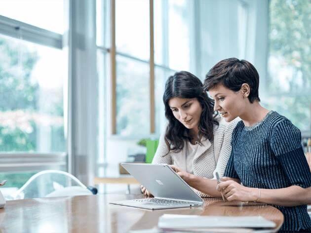 Dwie kobiety rozmawiają, patrząc na ekran komputera.