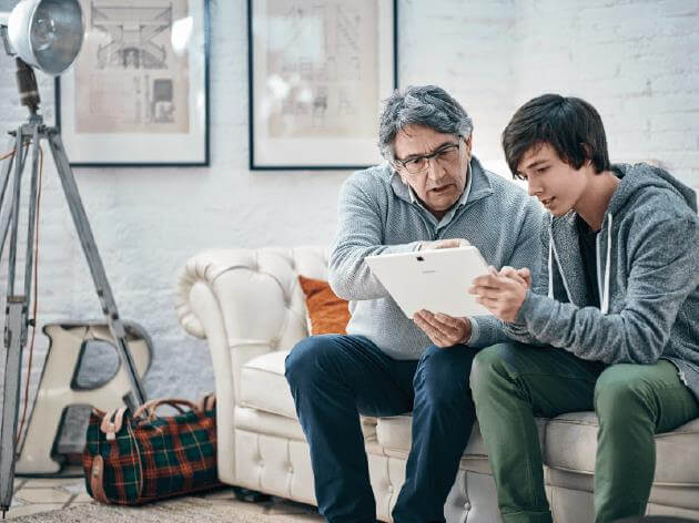 Eine ältere und eine jüngere Person sprechen miteinander, während sie auf ein Tablet schauen.