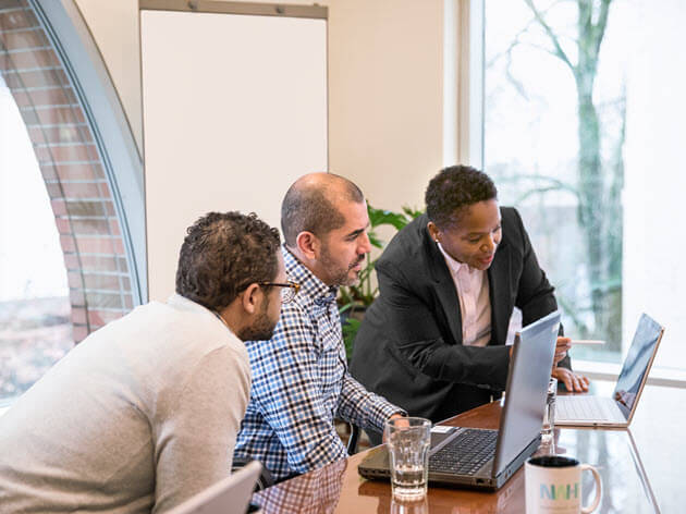 Três pessoas olham para seus computadores enquanto conversam.