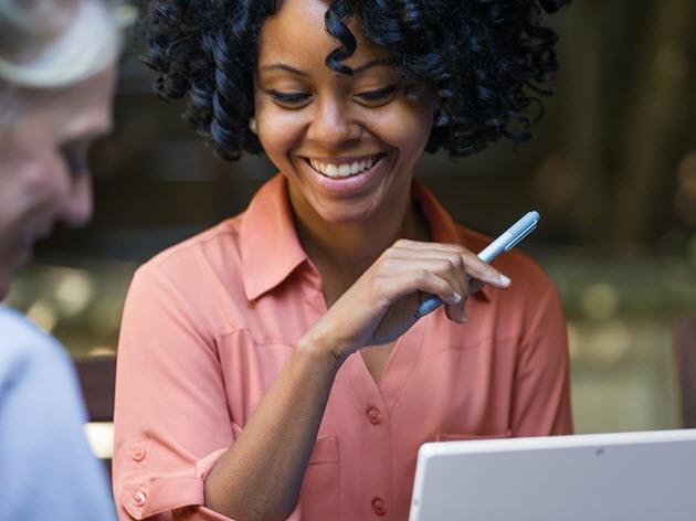 Uma mulher olha para baixo para seu computador e sorri.