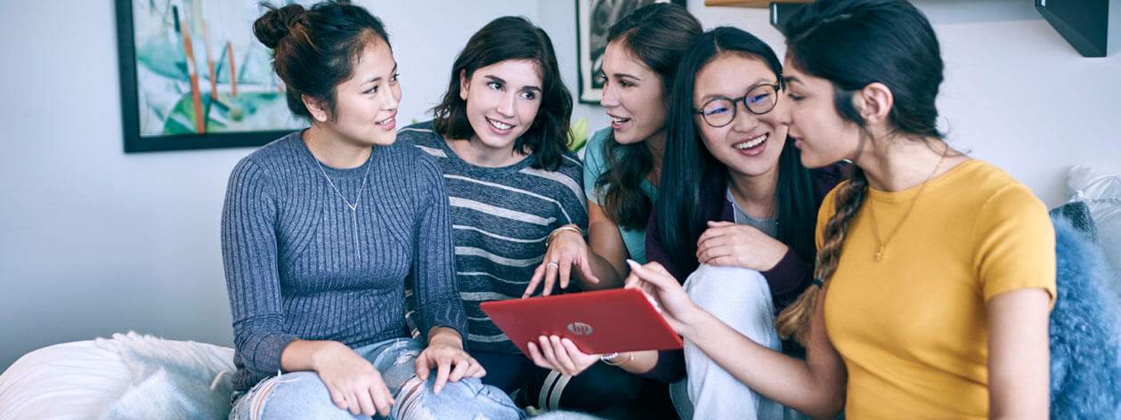 Five young women laugh as they look at a computer tablet