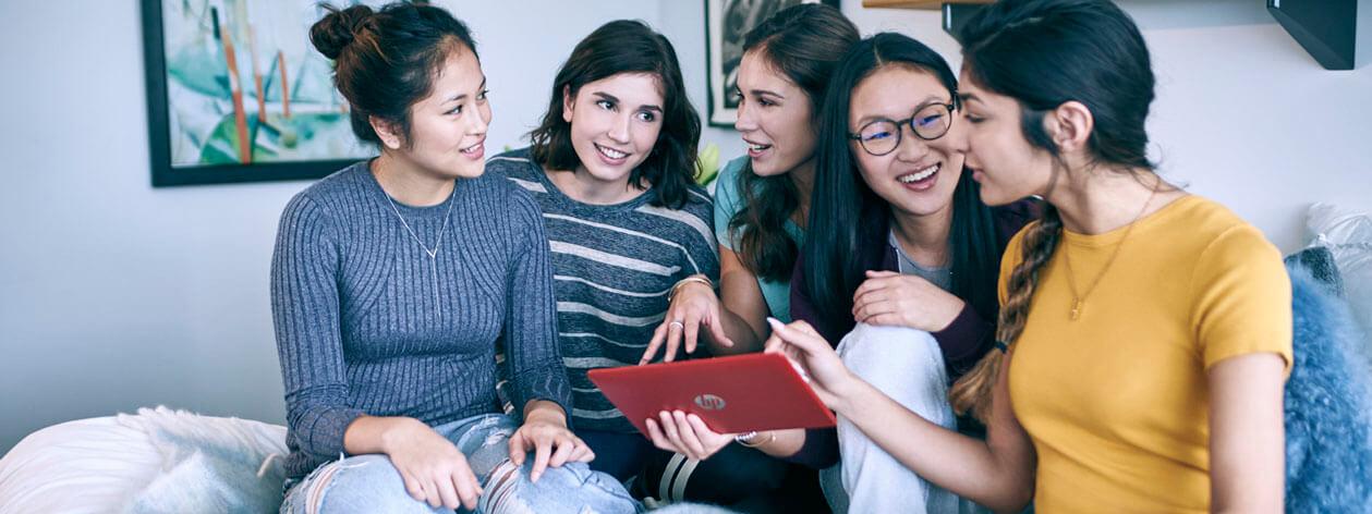 Cinco jovens mulheres sorrindo enquanto olham para um computador tablet
