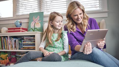 Mãe e filha olham para um Surface.