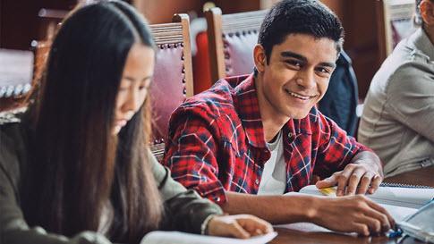 Um aluno olha para seus livros na câmera