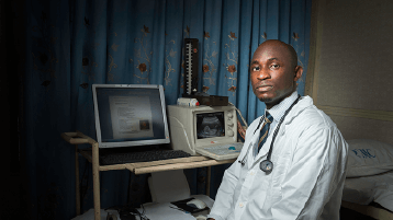 Man sits infront of medical imagering equipment