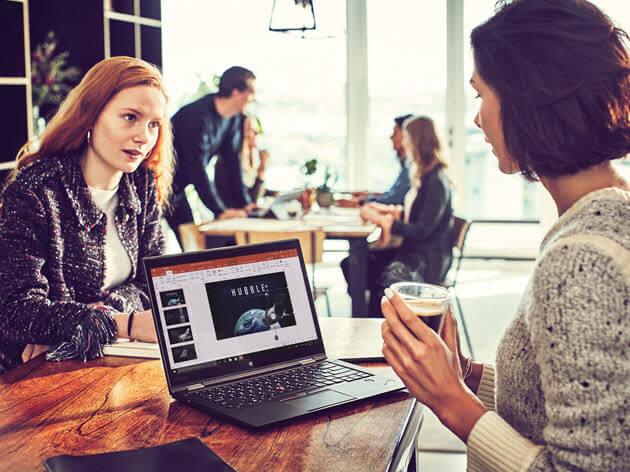 Två kvinnor pratar på ett kafé över en dator som visar en bild av Hubble-teleskopet.
