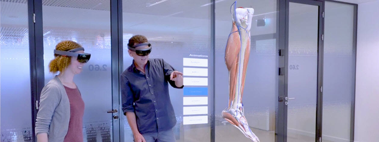 Two people wearing Microsoft HoloLens headsets look at a holographic human leg muscles, tendons and bones.