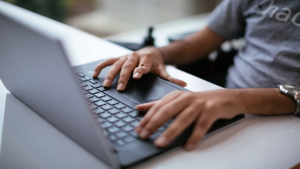 A man in a wheelchair with mobility impairment typing on a laptop. Accessibility and disability collection.
