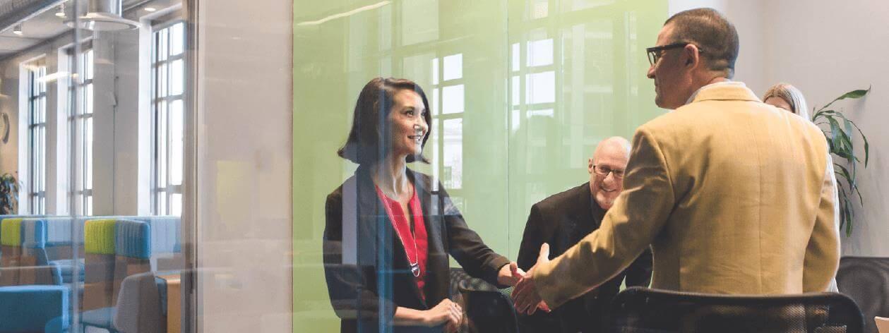 Hombres y mujeres se saludan y sonríen en una sala de conferencias.