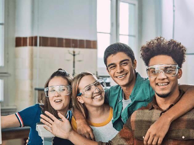 Quatro estudantes sorriem enquanto usam óculos de proteção.