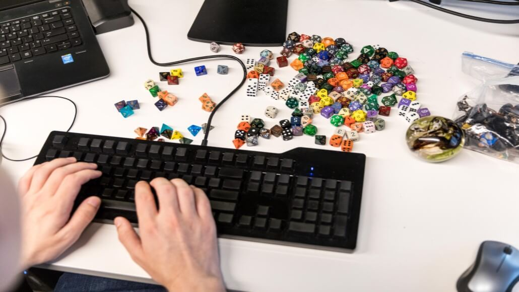 Close-up of two hands using a black keyboard on a white desk. Dozens of dice strewn in front of keyboard. Laptop keyboard partially shown in left upper corner. Large marble object and small plastic bag filled with small unidentifiable items shown at right.