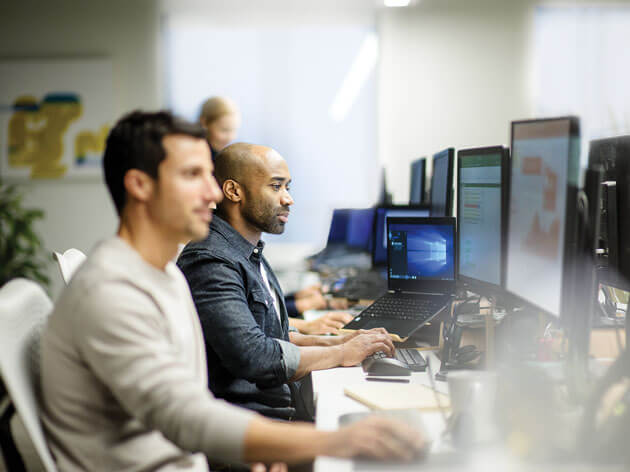 컴퓨터 앞에 나란히 앉은 남성 두 명
