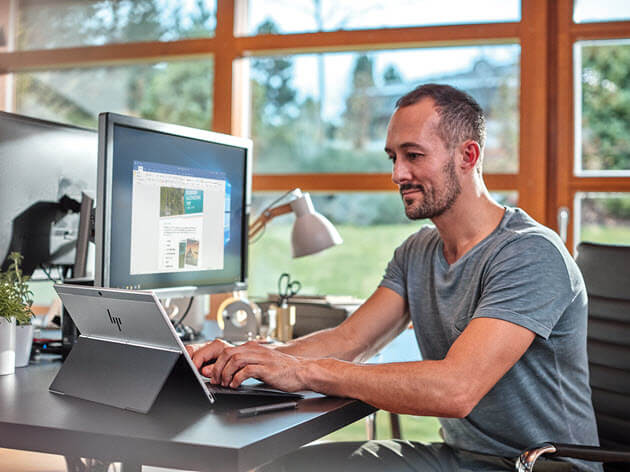 Man with laptop in a home office setting.