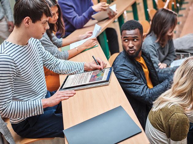 Ein Student macht sich mit einem Stift auf einem Laptop Notizen.