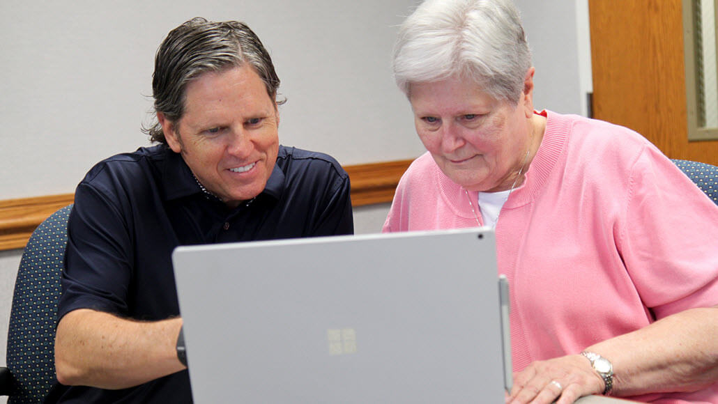 Two people look at a computer together.