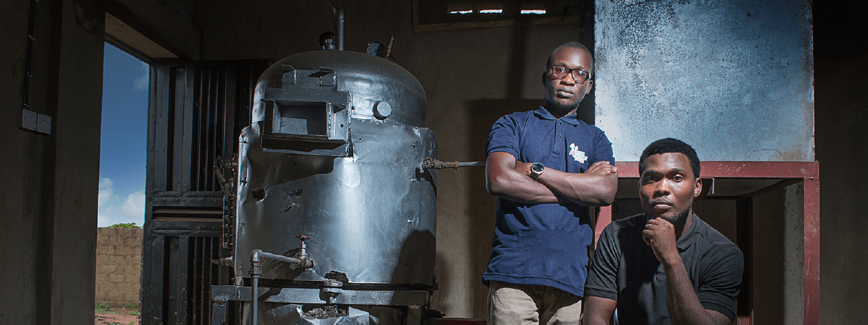 Two men pose in front of a water boiler