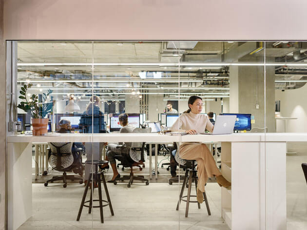 Eine Frau sitzt in einem modernem Büro.