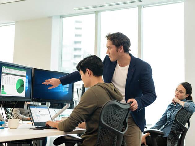 Ein Mann zeigt auf den Bildschirm, während ein anderer Mann am Schreibtisch sitzt.