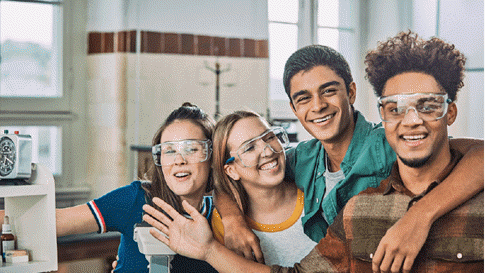Four smiling students wearing safety googles