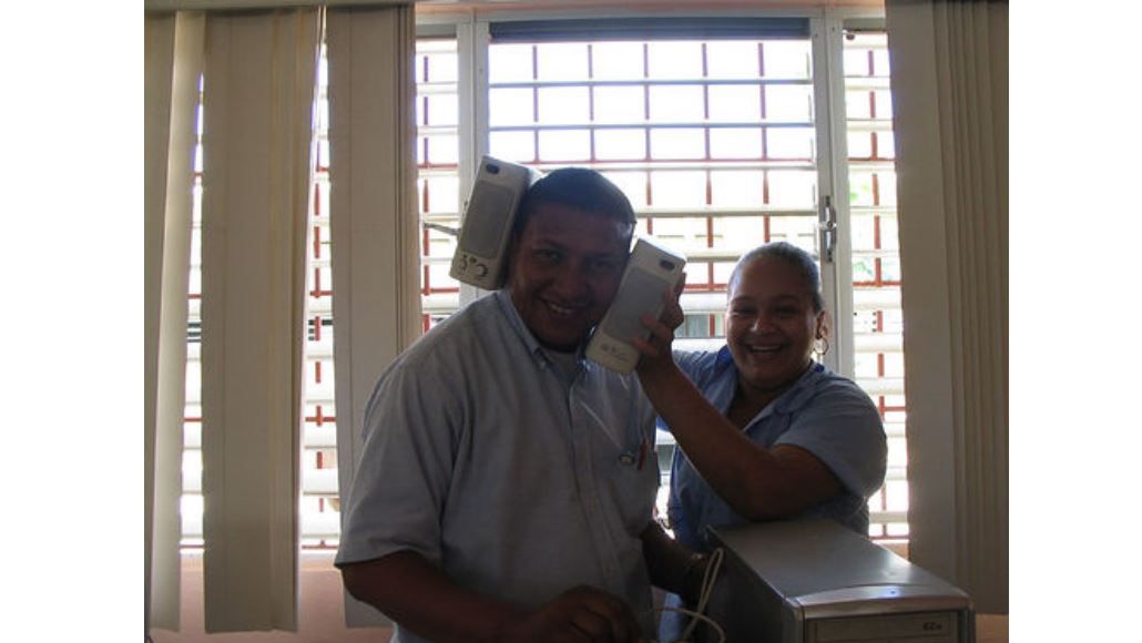 A couple smiling at the camera. The woman is holding speakers around the man's head.