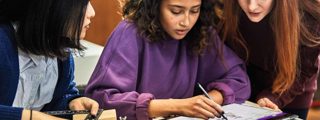 Studentinnen, die an einem Projekt arbeiten und Notizen auf dem Laptop machen.