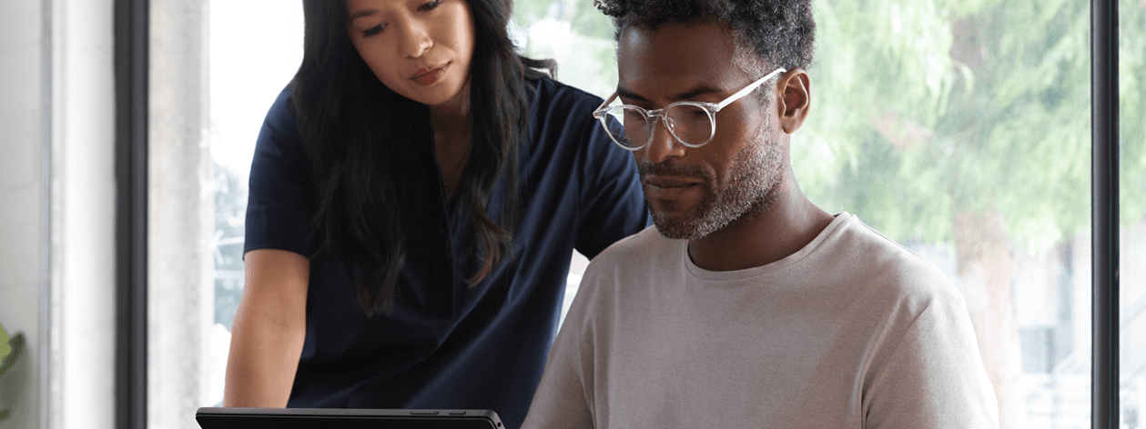Contextual image of man and woman collaborating while working on Black Surface Pro 6 inside office.