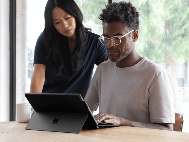 Two people look at Surface laptop.