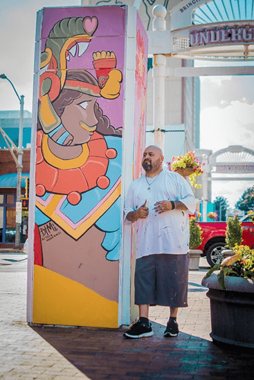 Dan leaning against a pillar painted with a mural of one of his characters.