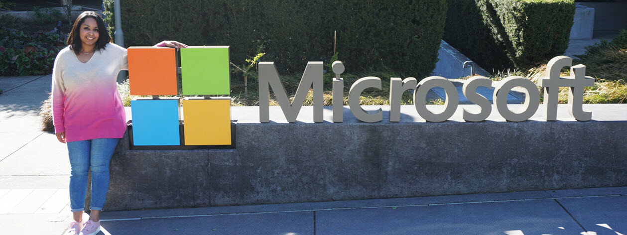 Woman standing next to a sign that reads Microsoft.
