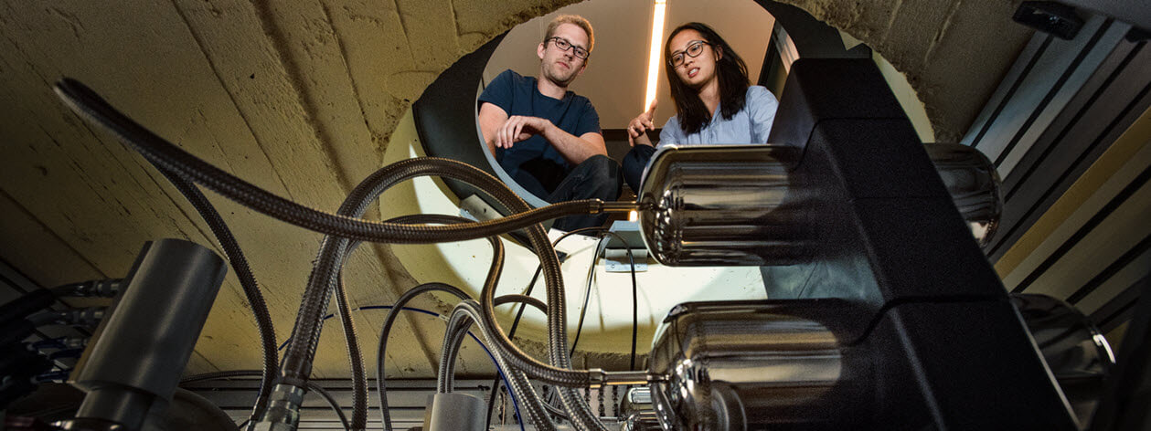 Male and female scientists observe quantum computing equipment.