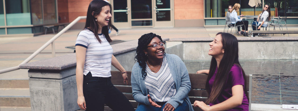 Three of the 2018 Women in Computing Award winners are sitting on a bench and laughing together.