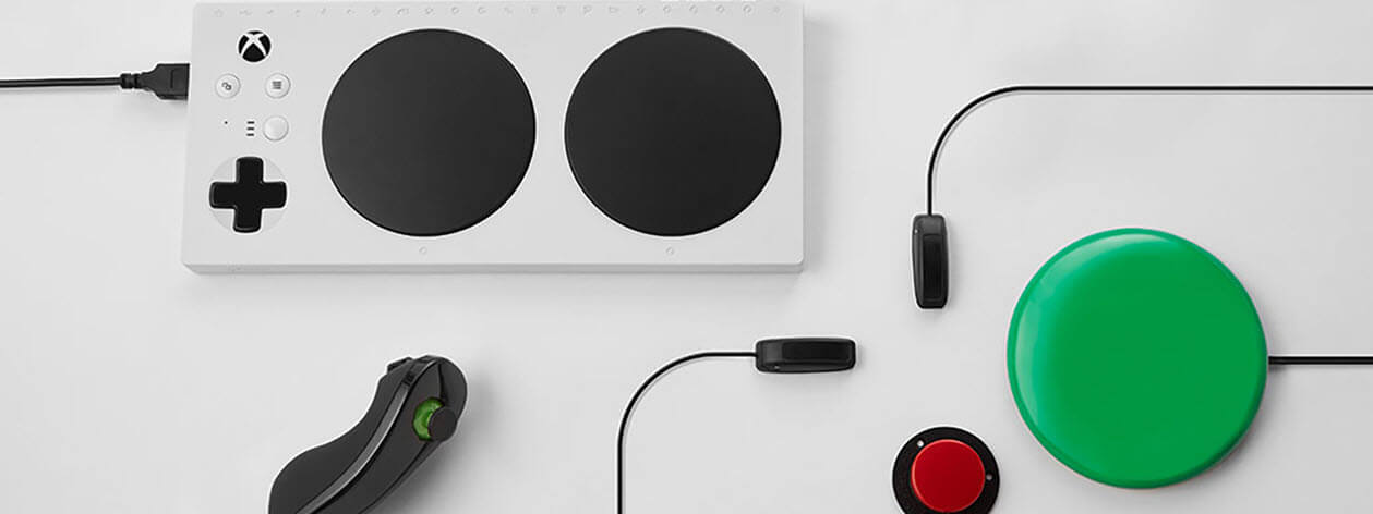 Adaptive controller elements spread out on white table.