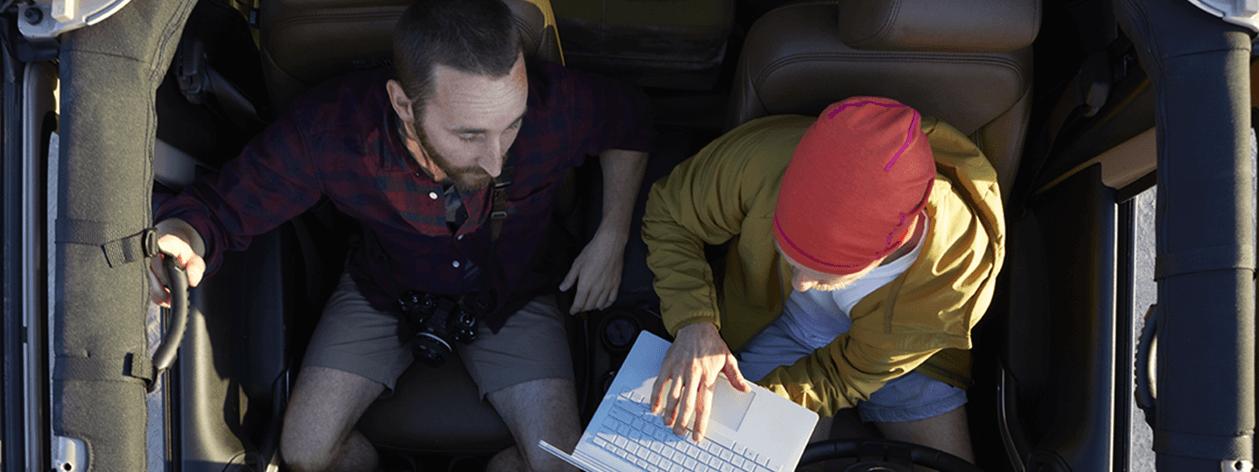 Hai người đàn ông cùng nhìn vào một chiếc máy tính xách tay khi đang ngồi trên một chiếc xe jeep.