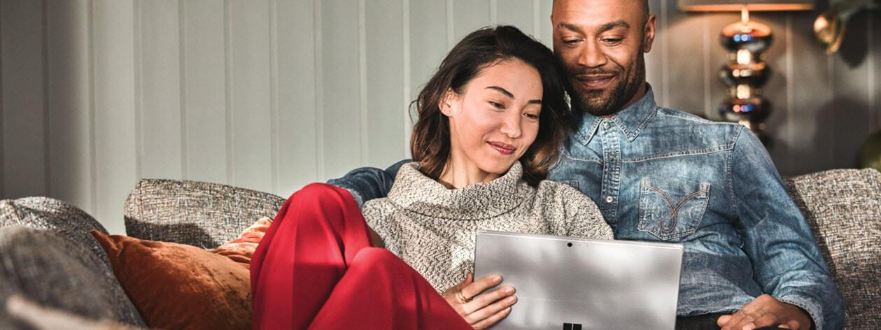 Một người đàn ông và một người phụ nữ đang ngồi trên ghế đi-văng và tương tác với chiếc máy tính xách tay Surface Pro.