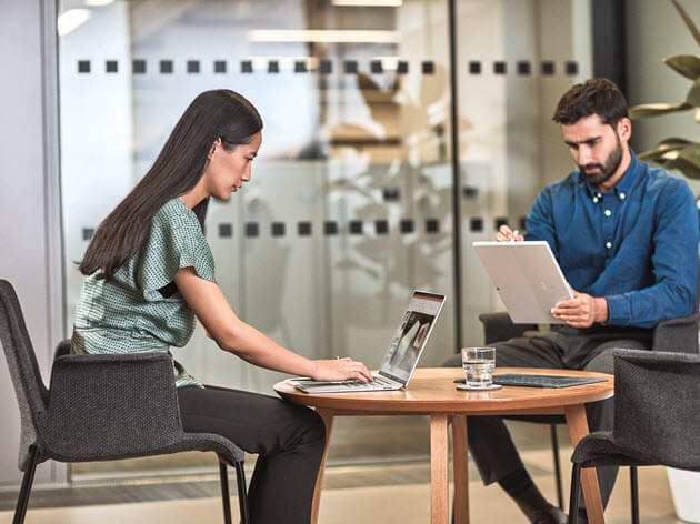 Man and woman, sitting at table, interacting with a Surface Pro laptop.